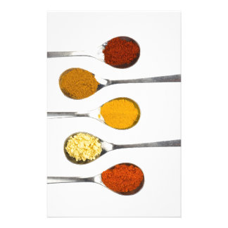 Various seasoning spices on metal spoons stationery