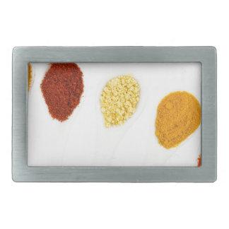 Various seasoning spices on porcelain spoons rectangular belt buckle