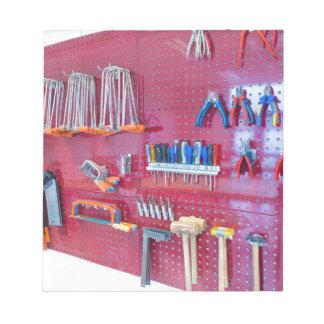 Various tools hanging at wall in high school notepad
