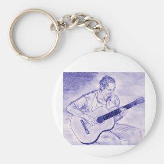Varón que toca la guitarra acústica mientras que s llavero redondo tipo pin