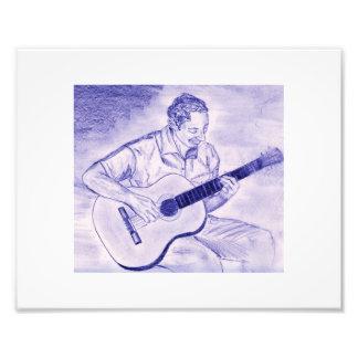 Varón que toca la guitarra acústica mientras que s fotografia