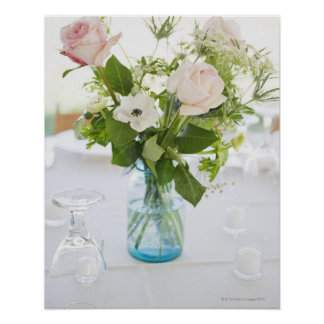 Vase of roses on set dinner table with glasses poster
