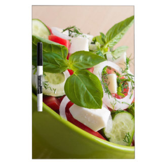 Vea el primer en un cuenco verde con una ensalada pizarras blancas