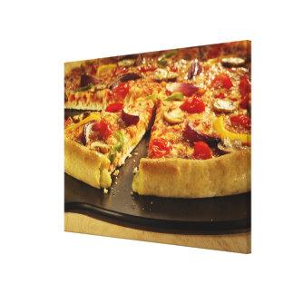 Vegetable pizza sliced on black pan on wood canvas print