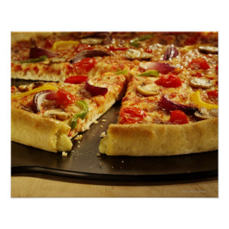 Vegetable pizza sliced on black pan on wood poster