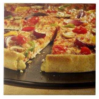 Vegetable pizza sliced on black pan on wood tile