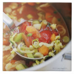 Vegetable soup in pan large square tile