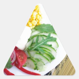 Vegetarian dish of raw vegetables and mozzarella triangle sticker