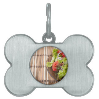 Vegetarian salad from fresh vegetables on a bamboo pet name tag