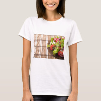 Vegetarian salad from fresh vegetables on a bamboo T-Shirt