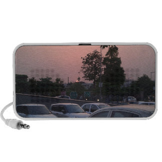 Vehicles in a parking lot at sunset travel speakers
