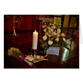 Vela y flores en piso de madera tarjeton