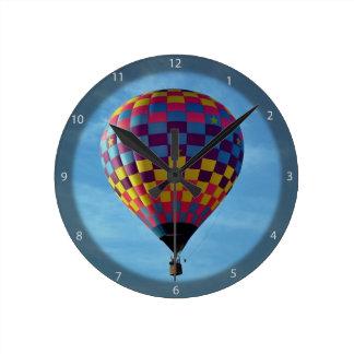 Velas de globo del aire caliente lejos en el cielo reloj redondo mediano
