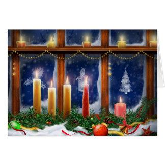 Velas en la tarjeta de Navidad de la ventana