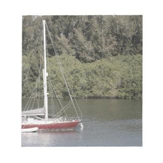 Velero rojo en árboles del río detrás libreta para notas