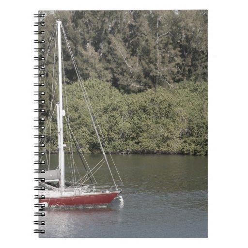 Velero rojo en árboles del río detrás cuaderno