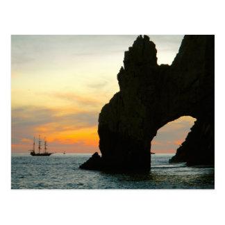 Velero tradicional en la puesta del sol, arcos de tarjetas postales