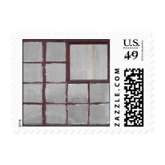 Ventana de madera de la fábrica vieja en un fondo sellos postales