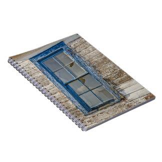 Ventana vieja con la pintura azul resistida notebook