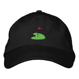Verde del golf con la bandera gorra de beisbol