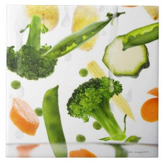 Verduras frescas con agua que cae en un cuenco azulejo cuadrado grande