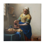 """Vermeer The Milkmaid Tile<br><div class=""""desc"""">Johannes Vermeer The Milkmaid tile. Oil painting on canvas circa 1660. A beautiful depiction of a Dutch kitchen, Vermeer's The Milkmaid captures middle class northern European life with grace and mastery. The milkmaid pours milk from one jar into a larger pot surrounded by various loaves of fresh bread, a blue...</div>"""