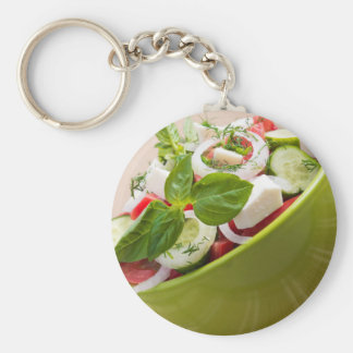 Vertical view close-up on a green bowl with salad keychain