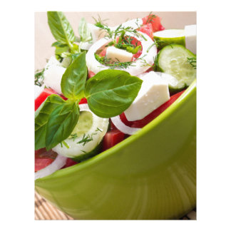 Vertical view close-up on a green bowl with salad letterhead