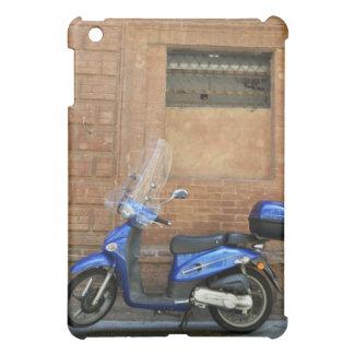 Vespa de motor azul por la pared roja, Siena, Ital