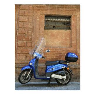 Vespa de motor azul por la pared roja, Siena, Postal