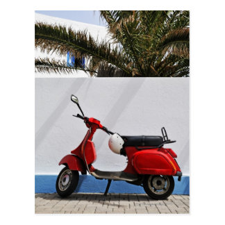 Vespa de motor roja por la pared, isla de postal