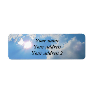 Vibrant blue sky with sun and clouds photo label