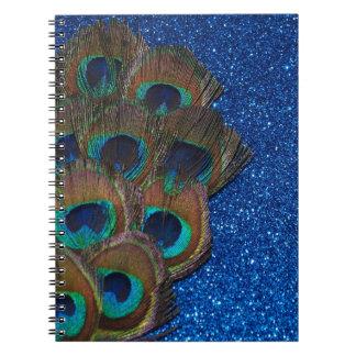 Vida reluciente del ramo azul del pavo real aún libros de apuntes con espiral
