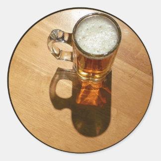 Vidrio de cerveza en la tabla pegatina redonda