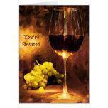Vidrio de vino, uvas, luz de una vela le invitan felicitacion