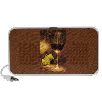 Vidrio de vino y de uvas verdes en luz de una vela altavoces de viajar