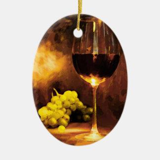Vidrio de vino y de uvas verdes en luz de una vela adorno