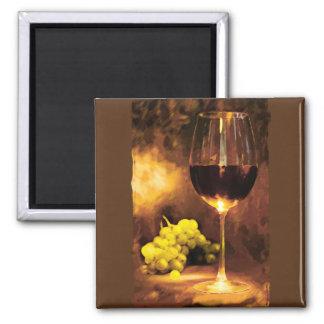 Vidrio de vino y de uvas verdes en luz de una vela imán para frigorifico