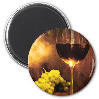 Vidrio de vino y de uvas verdes en luz de una vela imanes para frigoríficos
