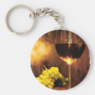 Vidrio de vino y de uvas verdes en luz de una vela llavero redondo tipo pin