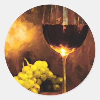 Vidrio de vino y de uvas verdes en luz de una vela pegatina redonda