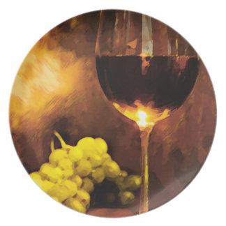Vidrio de vino y de uvas verdes en luz de una vela plato