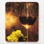 Vidrio de vino y de uvas verdes en luz de una vela alfombrillas de raton