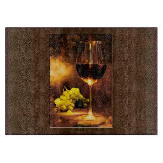 Vidrio de vino y de uvas verdes por luz de una vel