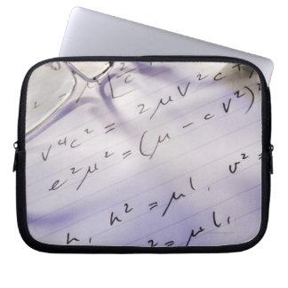 Vidrios, pluma y símbolos matemáticos en el papel, funda computadora