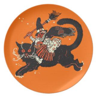 Vieja bruja del vintage que monta un gato negro platos para fiestas