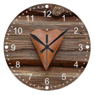 Viejo corazón rústico en la madera de la cabaña de reloj redondo grande