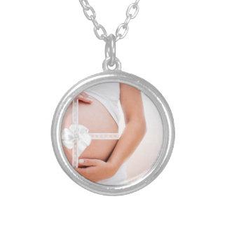 Vientre embarazada envuelto en una cinta blanca colgante redondo