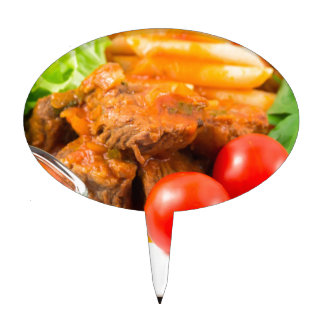 View close-up on a meal of beef stew with pasta cake topper