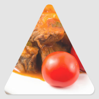 View close-up on a meal of beef stew with pasta triangle sticker